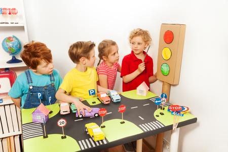 Vier kinderen, vijf jaar oud jongens en meisje, studeren of Highway Traffic code met de hand gemaakte kartonnen licht-signaal en de weg speelveld Stockfoto