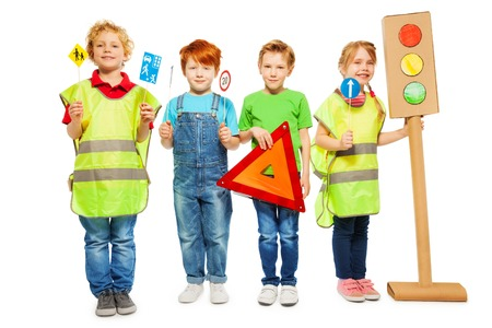 Four kids in high visibility jackets standing in a row, holding warning triangle, road signs and light-signal models, isolated on white