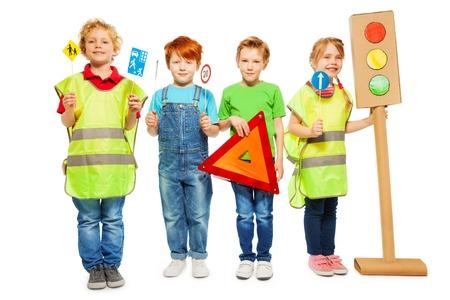 Vier kinderen in hoge zichtbaarheid jassen staan in een rij, met gevarendriehoek, verkeersborden en licht-signaal modellen, geïsoleerd op wit