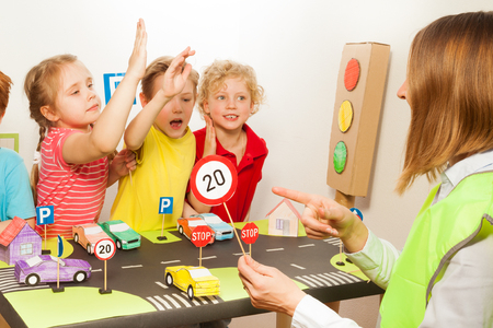 road safety: Smart pupils all raising their hands up, while their teacher pointing to the speed-limit sign icon at the road safety class