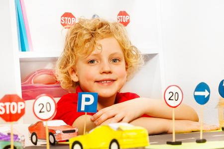 paso de peatones: Sonriente jugando preescolar controlador de pelo rubio con los coches de juguete y las señales de tráfico en el jardín de infancia