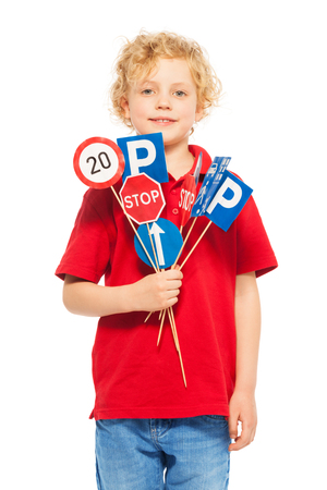 leading education: Cute seven years old boy in red t-shirt holding small miniatures of road signs, isolated on white