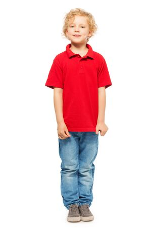 5 years: Full-length portrait of blond curly-haired kid boy in red polo shirt and denim, isolated on white