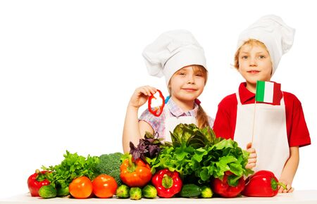 Two happy kids, boy and girl in cooks uniform preparing fresh vegetables, holding Italian flag isolated on white