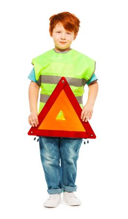warning vest: Full-length portrait of redheaded five years old boy, wearing high visibility vest and holding warning triangle, isolated on white