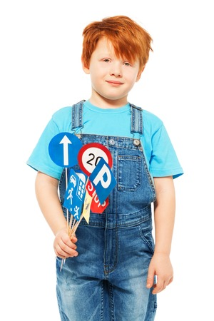 redheaded: Redheaded five years old boy in blue t-shirt and overall, holding set of toy road signs, isolated on white
