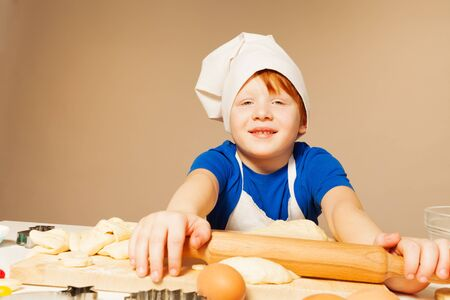ware: Portrait of redheaded boy in bakers uniform, flattening dough, sitting against background with copy space
