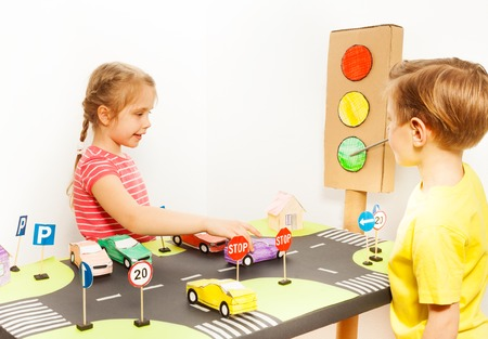 road safety: Little girl driving toy car on road playing field, while her friend pointing to the green signal of the handmade light with a pointer in road safety class