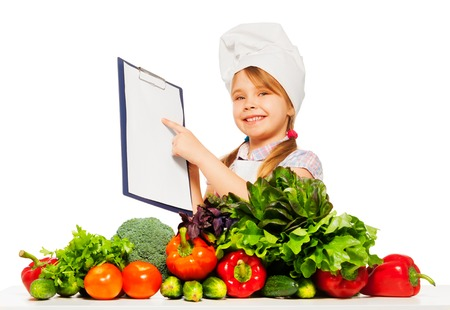blanked: Happy smiling girl in cooks uniform holding blanked clipboard, standing behind the table full of fresh vegetables, isolated on white