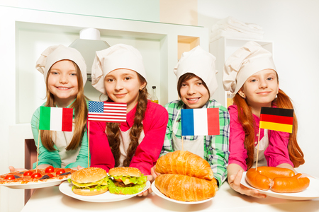 Four happy kids in cooks uniform representing traditional meal of European countries and USA