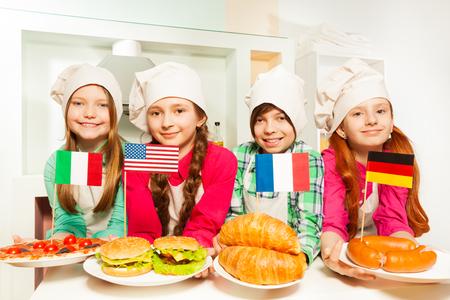 Vier gelukkig kinderen in uniform kok die traditionele maaltijd van de Europese landen en de VS
