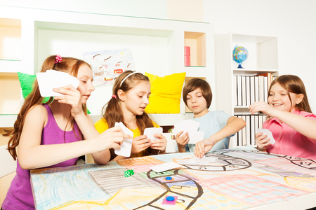 Four friends, ten years old kids, sitting at the table, playing the tabletop game with cards Foto de archivo