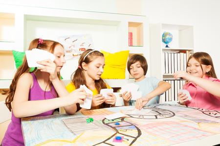 Vier vrienden, tien jaar oude kinderen, zitten aan de tafel, spelen het tafelbladspel met kaarten