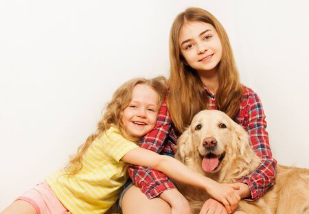 adult sisters: Two smiling sisters hugging with their adult Golden Retriever sitting against white background with copy-space