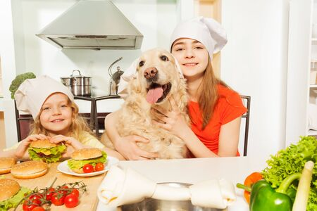 ration: Two smiling girls with their pet in cooks hats preparing meal in the kitchen
