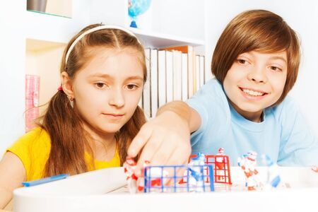 young boys: Two kids, boy and girl playing ice hockey table board game in the playroom Stock Photo