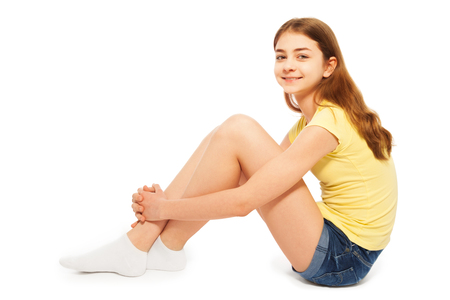 thirteen: Side view of teenage girl in denim shorts and yellow t-shirt, sitting on the floor, isolated on white background