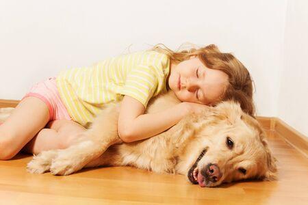 five years': Sleeping five years old girl, lying on the room floor, hugging her Golden Retriever doggy