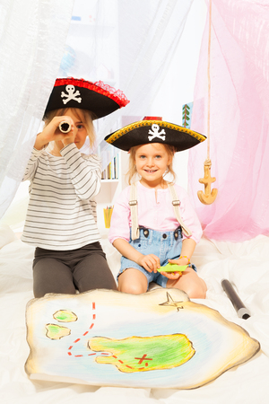 Two cute girls in costumes of pirates looking through a toy spyglass Stock Photo