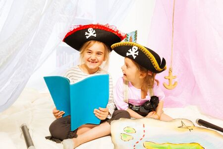 Two happy girls in pirates costumes, reading blanked book about pirates treasures Stock Photo