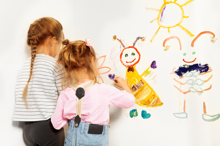 Two little painters, preschool girls drawing funny picture at the wall, isolated on white