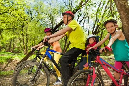 bicicleta: familia deportiva de cuatro personas montando en bicicleta en el parque soleado de primavera Foto de archivo