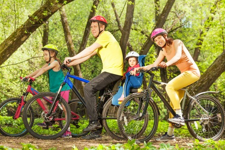 touring: Active family on bikes riding in spring sunny forest, mother, father and two age-diverse daughters together