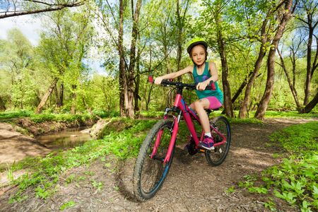 cycling mountain: Young girl in bicycle helmet cycling mountain bike on the forest trail in the spring time