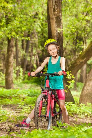 Happy girl cyclist in bicycle helmet, relaxing at spring park, sitting on her bike Stock Photo