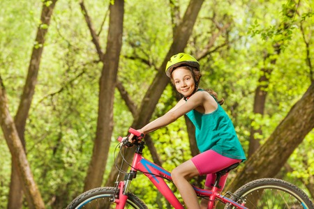 Side view portrait of smiling young girl in bicycle helmet, cycling through sunny woodland