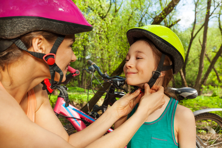 Active mother helping her daughter to clasp bicycle helmet before cycling
