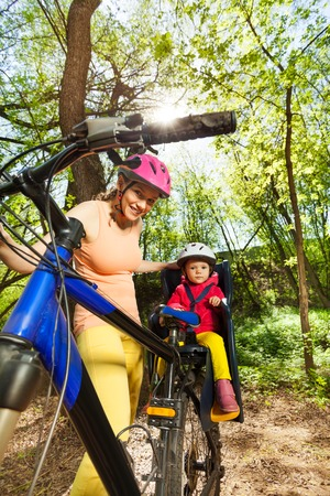 enfant banc: Sporty woman riding her little daughter in bicycle seat on forest trail