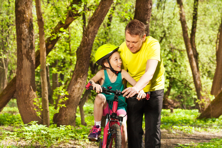 Father helping his young daughter in bicycle helmet to cycle in the spring park