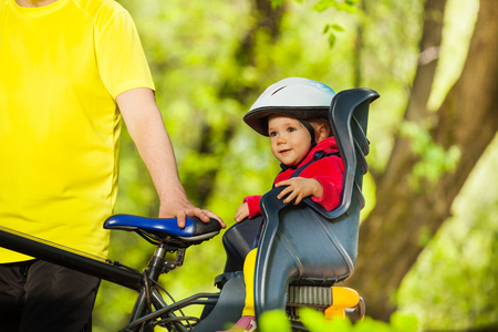helmet seat: Portrait of little girl in bicycle helmet sitting in bike child seat during cycling in sunny forest