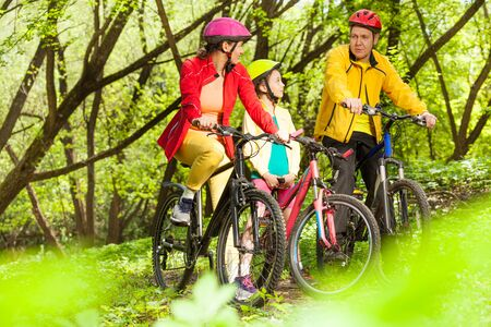 Sports family, mother, father and girl, having fun cycling in the sunny spring woodland