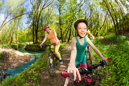 Portrait of happy teenage girl, cycling with her mother by the side of the river in the spring woods