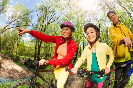Portrait of happy active family with bikes finding their way in the spring wood, pointing with fingers Stock Photo