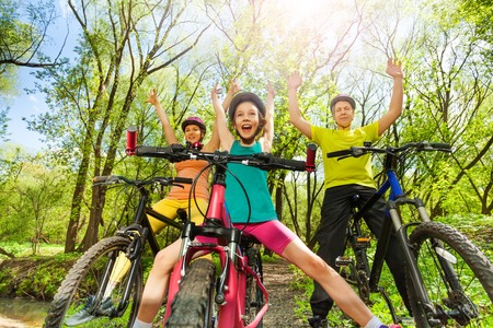 family activities: Bottom view of funny girl with parents having fun cycling in the sunny spring wood Stock Photo