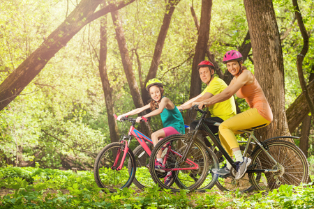 Side view of happy smiling family on mountain bikes in the spring sunny forest