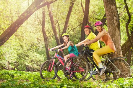 Zijaanzicht van gelukkige lachende familie op mountainbikes in het lente zonnige bos Stockfoto