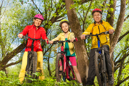Happy sporty family in bicycles helmets riding the bikes in the sunny spring park Stock Photo