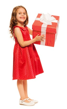 Nice little six years old girl standing with big red box present with white ribbon bow in full height portrait Stock Photo