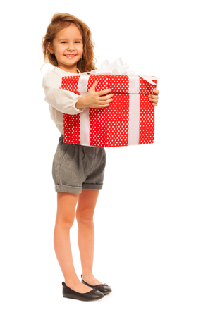 Nice little girl stand with Christmas present in big red box isolated on white in full height portrait