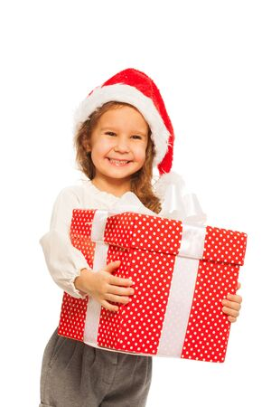 Happy close portrait of little girl with big red present with bow wearing Christmas Santa hat Stock Photo