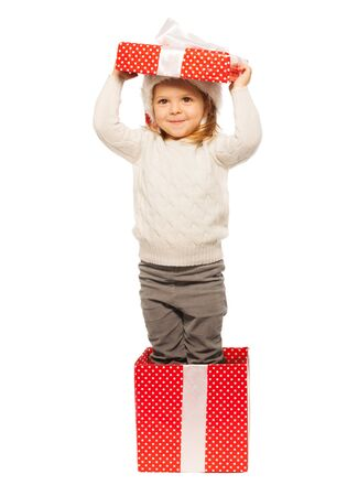 Smiling little girl hiding in the big present bright red box standing isolated on white