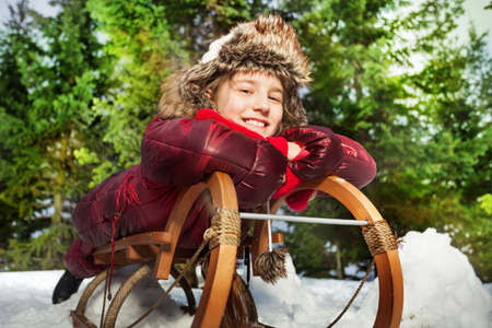 skids: Smiling girl having fun in winter snow on a sledge at the forest