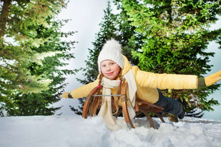 skids: Child girl riding a sledge outdoors in snowy forest