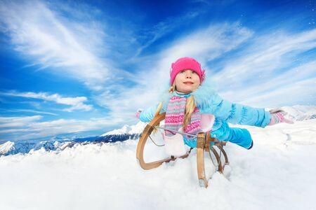 skids: Little girl in blue coat and pink hat on sledge and stretched hands in the mountain