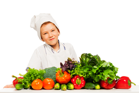 Happy kid boy in cooks uniform, preparing healthy vegetables meal, isolated on white background