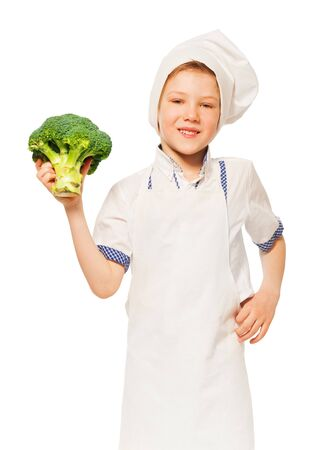 ration: Close-up portrait of smiling kid boy in cooks apron and toque, holding fresh broccoli, isolated on white